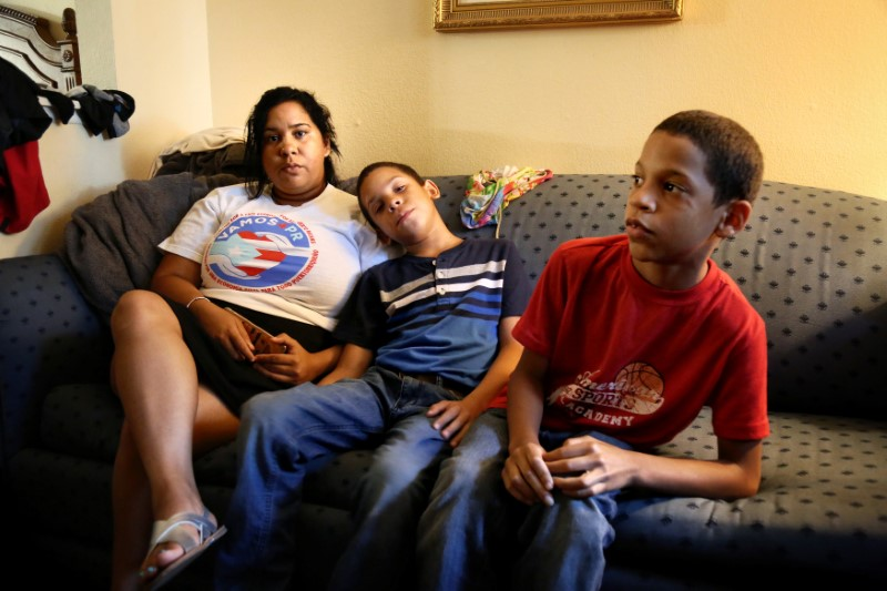 Jaykarey Skerett, a Puerto Rican mother whose home was destroyed by Hurricane Maria, sits with her two sons for an interview in her hotel room in Kissimmee, Florida, U.S. July 2 2018. Picture taken July 2, 2018. REUTERS/Joey Roule