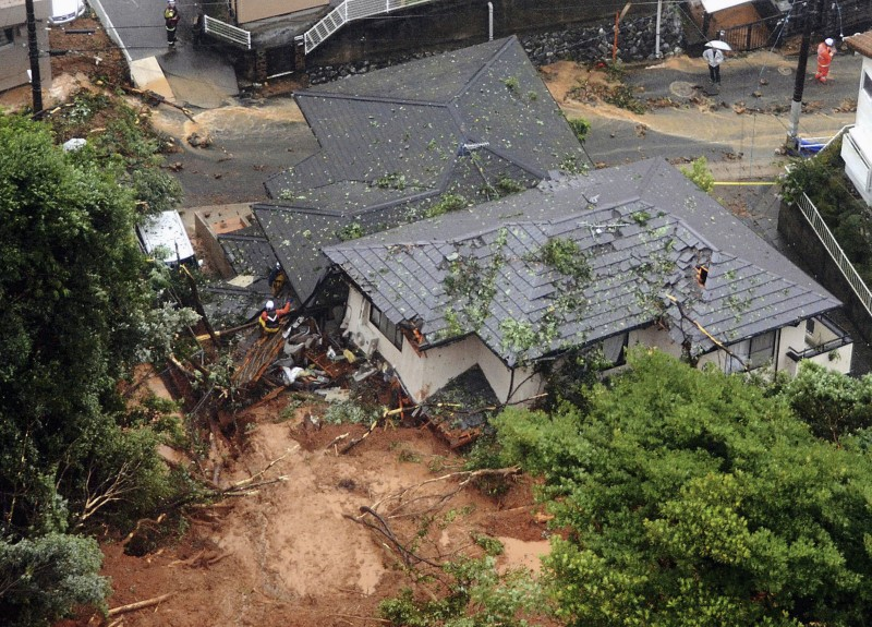 Rescue workers are seen next to houses damaged by a landslide following heavy rain in Kitakyushu, southwestern Japan, in this photo taken by Kyodo July 6, 2018. Mandatory credit Kyodo/via REUTE