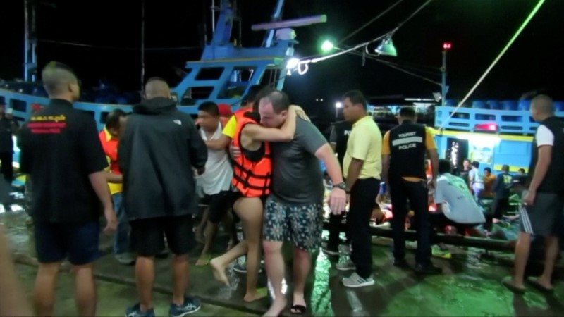 A rescued woman wearing a life jacket hugs a man after a boat capsized off the tourist island of Phuket, Thailand July 5, 2018 in this still image taken from video. Video taken July 5, 2018. REUTERS via Reuters TV