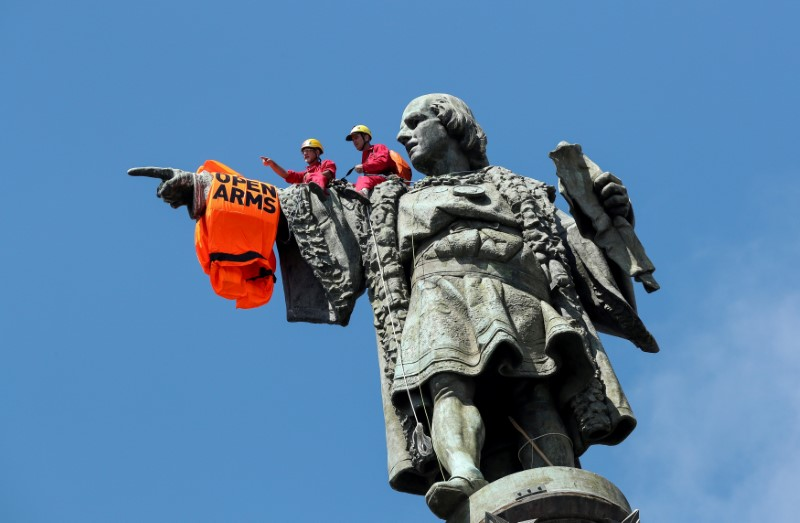 FILE PHOTO: Activists from the Spanish Proactiva Open Arms charity place a life jacket on the Christopher Columbus statue after the Open Arms rescue boat arrived at a port in Barcelona, Spain, carrying migrants rescued off Libya, July 4, 2018. REUTERS/Albert Gea/File Photo