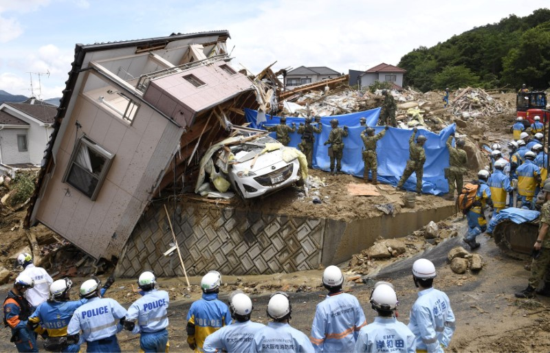 Rescue workers look for missing people in a house damaged by heavy rain in Kumano town, Hiroshima Prefecture, Japan, in this photo taken by Kyodo July 9, 2018. Mandatory credit Kyodo/via REUTERS
