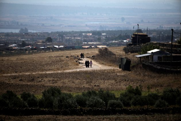 People walk near the Israel-Syria border line as it is seen from the Israeli-occupied Golan Heights, Israel July 7, 2018. REUTERS/Ronen Zvulun