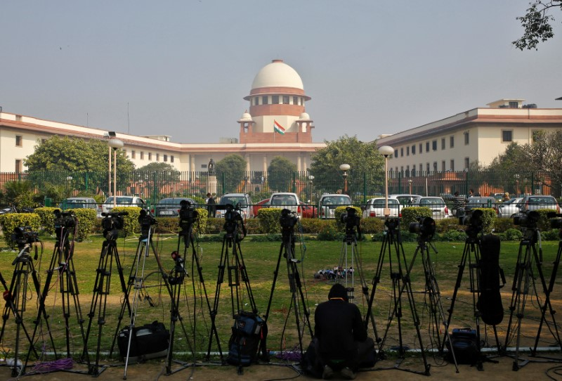 FILE PHOTO: A television journalist sets his camera inside the premises of the Supreme Court in New Delhi February 18, 2014. REUTERS/Anindito Mukherjee/File pho