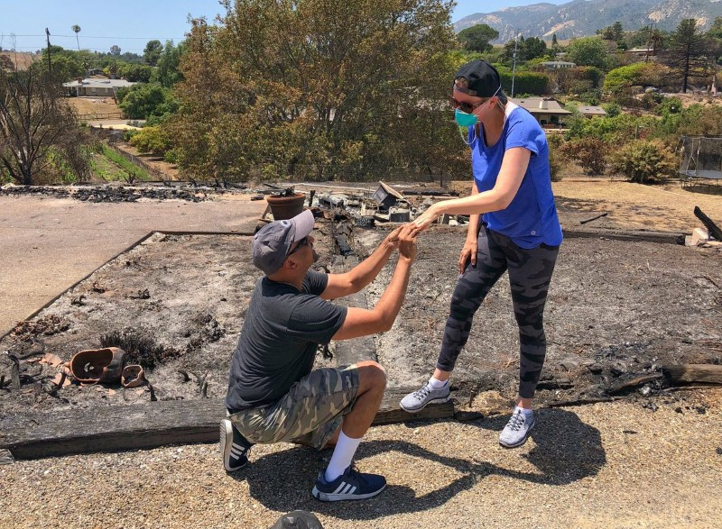 Ishu and Laura Rao, return to the rubble of their home which they lost in a wildfire, to retrieve their wedding ring, in Alameda, California, U.S., in this July 8, 2018 photo obtained from social media. MANDATORY CREDIT. Mike Eliason/Santa Barbara County Fire Department/via REUTERS