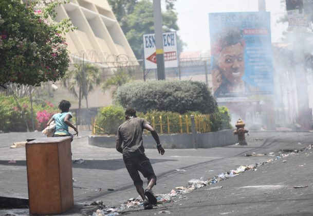 People run away as police uses tear gas to disperse people in a street of Port-au-Prince, Haiti, July 8, 2018. REUTERS/Andres Martinez Casares