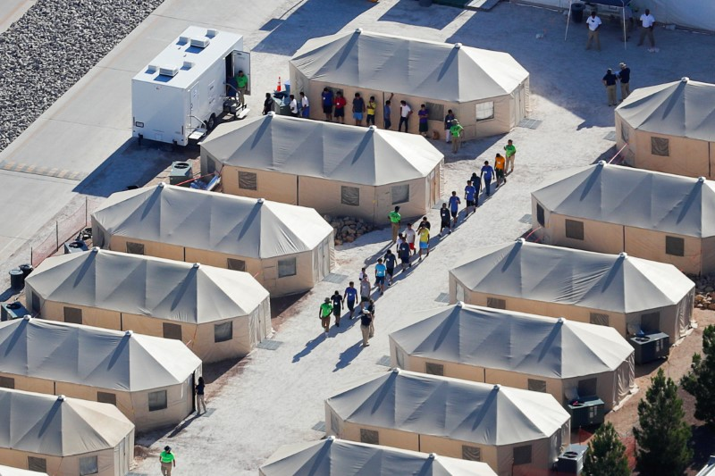 "FILE PHOTO: Immigrant children now housed in a tent encampment under the new ""zero tolerance"" policy by the Trump administration are shown walking in single file at the facility near the Mexican border in Tornillo, Texas, U.S. June 19, 2018. REUTERS/Mike Blake/File Photo"
