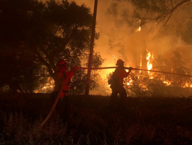 Firefighters work at the site of a wildfire in Goleta, California, U.S., July 6, 2018 in this image obtained on social media. Mike Eliason/Santa Barbara County Fire/via REUTERS