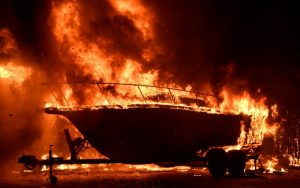 A boat burns as fast-moving wildfire that destroyed homes driven by strong wind and high temperatures forcing thousands of residents to evacuate in Goleta, California, U.S., early July 7, 2018. REUTERS/Gene Blevin