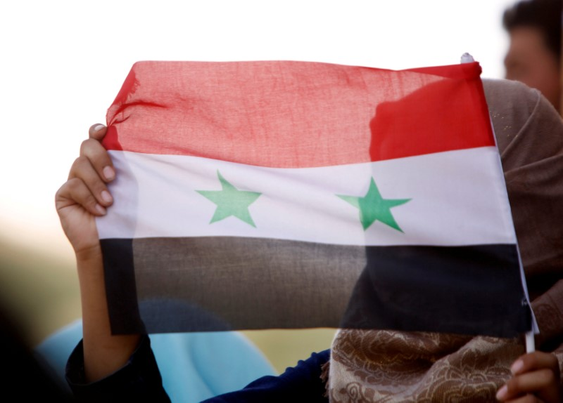 FILE PHOTO: A woman holds a Syrian flag in Deraa, Syria, July 4, 2018. REUTERS/Omar Sanadiki/File Photo