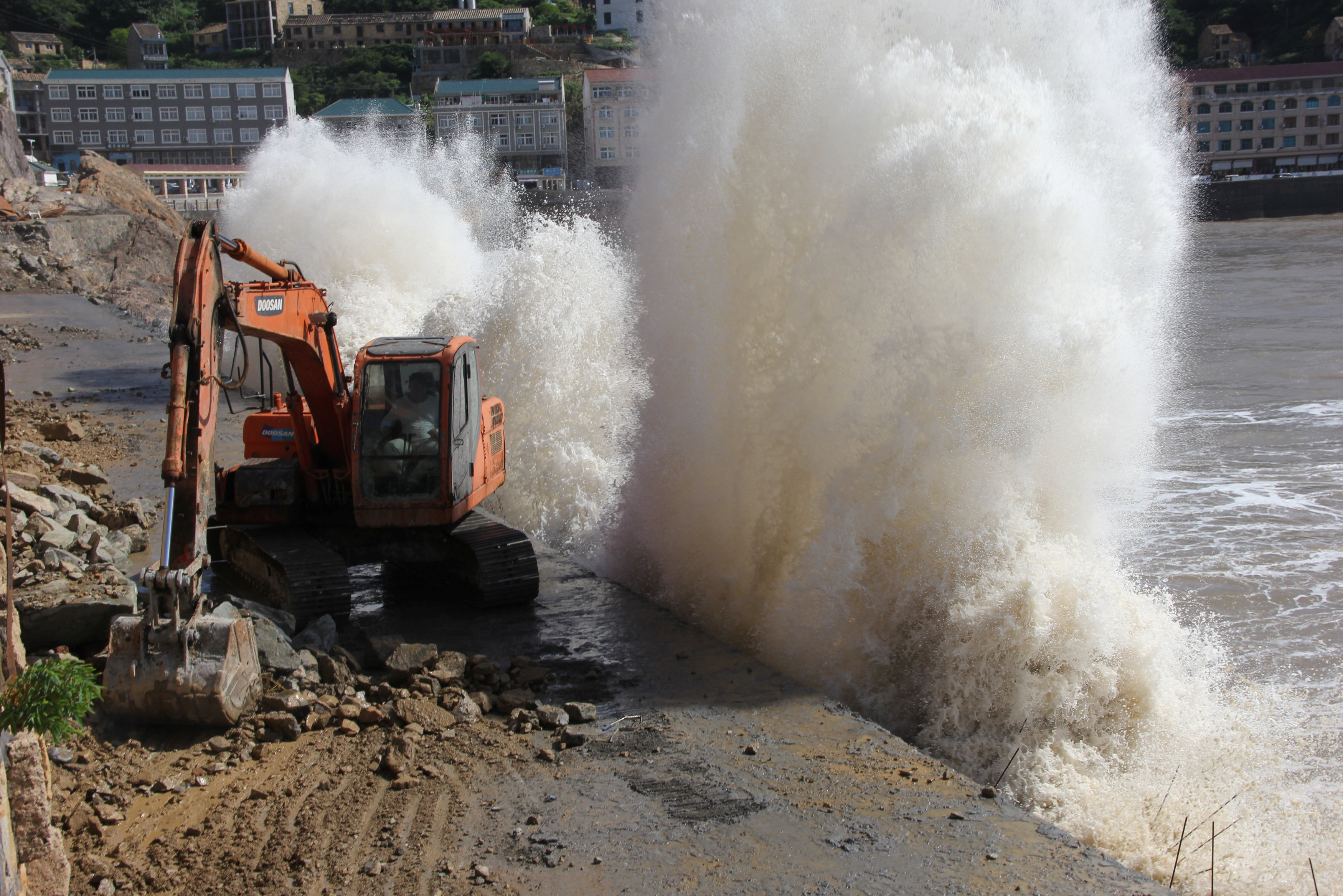 A wave breaks on the waterfront next to an excavator, as super typhoon Maria approaches, in Taizhou, Zhejiang province, China, July 10, 2018. REUTERS/Stringer