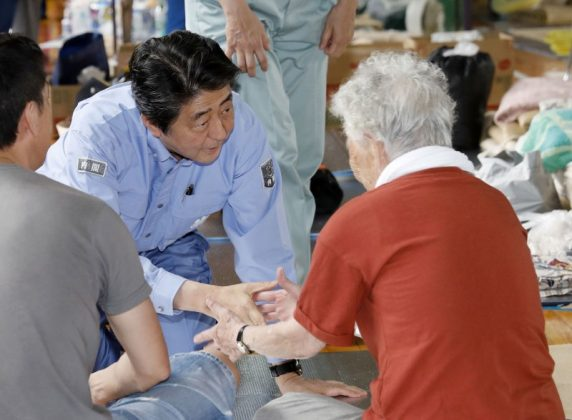 Japan's Prime Minister Shinzo Abe meets local residents staying at an evacuation center in Kurashiki, Okayama Prefecture, Japan, in this photo taken by Kyodo July 11, 2018. Mandatory credit Kyodo/via REUTERS