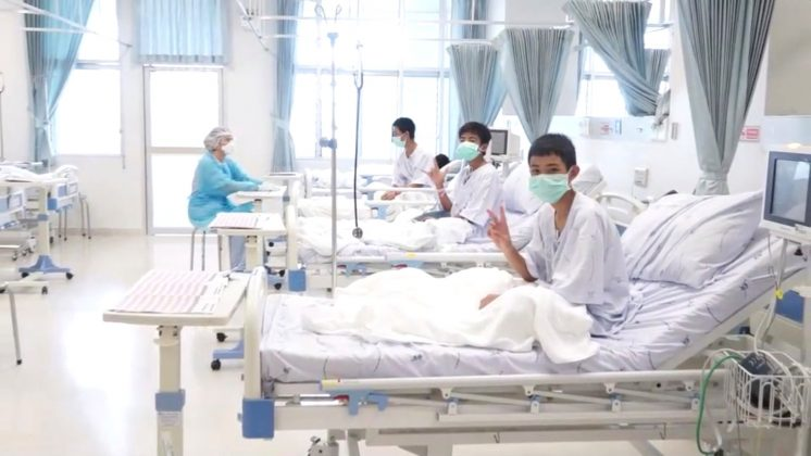 A screen grab shows boys rescued from the Thai cave wearing mask and resting in a hospital in Chiang Rai, Thailand from a July 11, 2018 handout video. Government Public Relations Department (PRD) and Government Spokesman Bureau/Handout via REUTERS TV