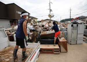 Local residents try to clear debris at a flood affected area in Mabi town in Kurashiki, Okayama Prefecture, Japan, July 12, 2018. REUTERS/Issei Kato