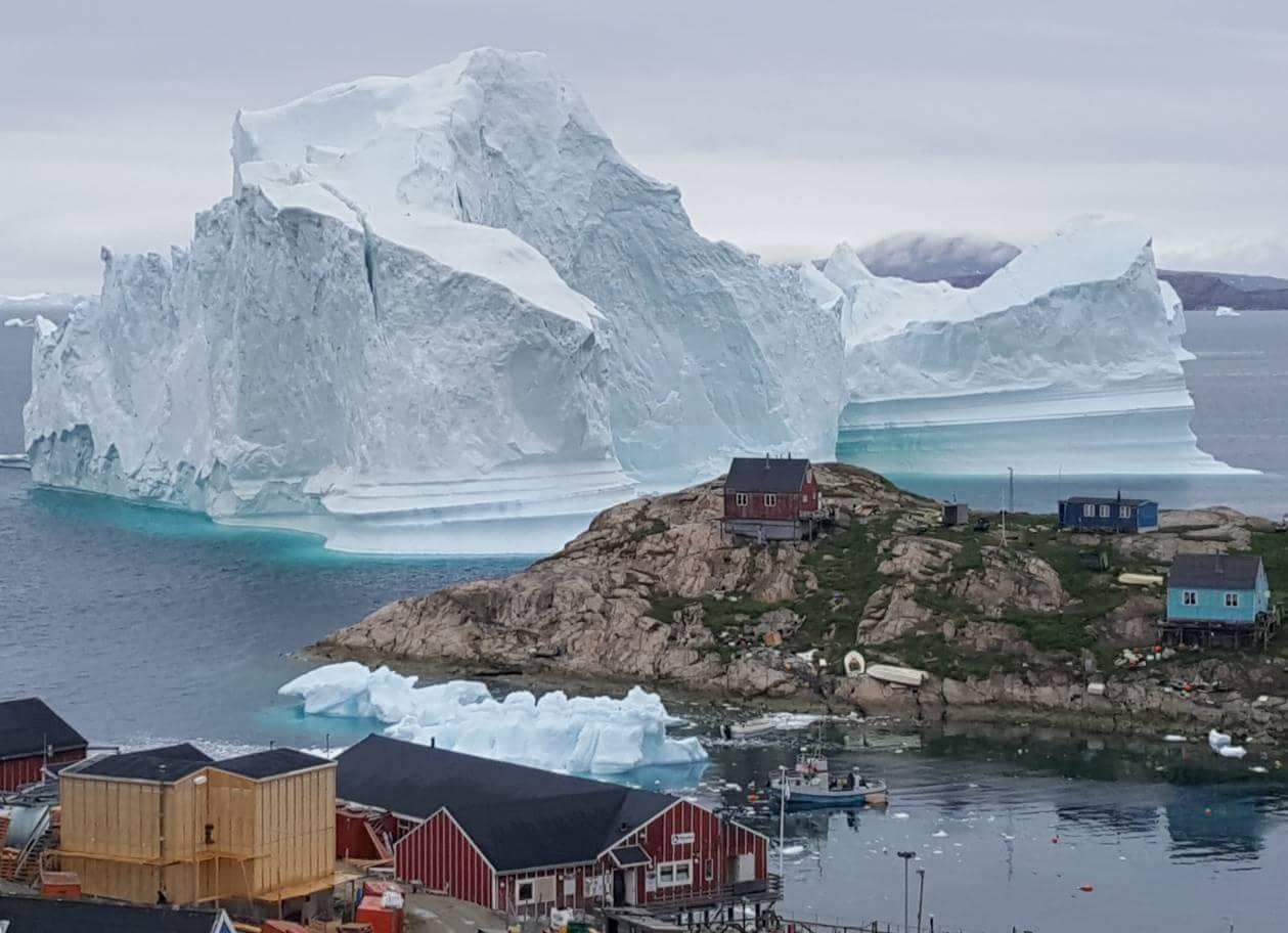 A giant iceberg is seen behind an Innaarsuit settlement, Greenland July 12, 2018. Picture taken July 12, 2018. Ritzau Scanpix/Karl Petersen/ via REUTERS