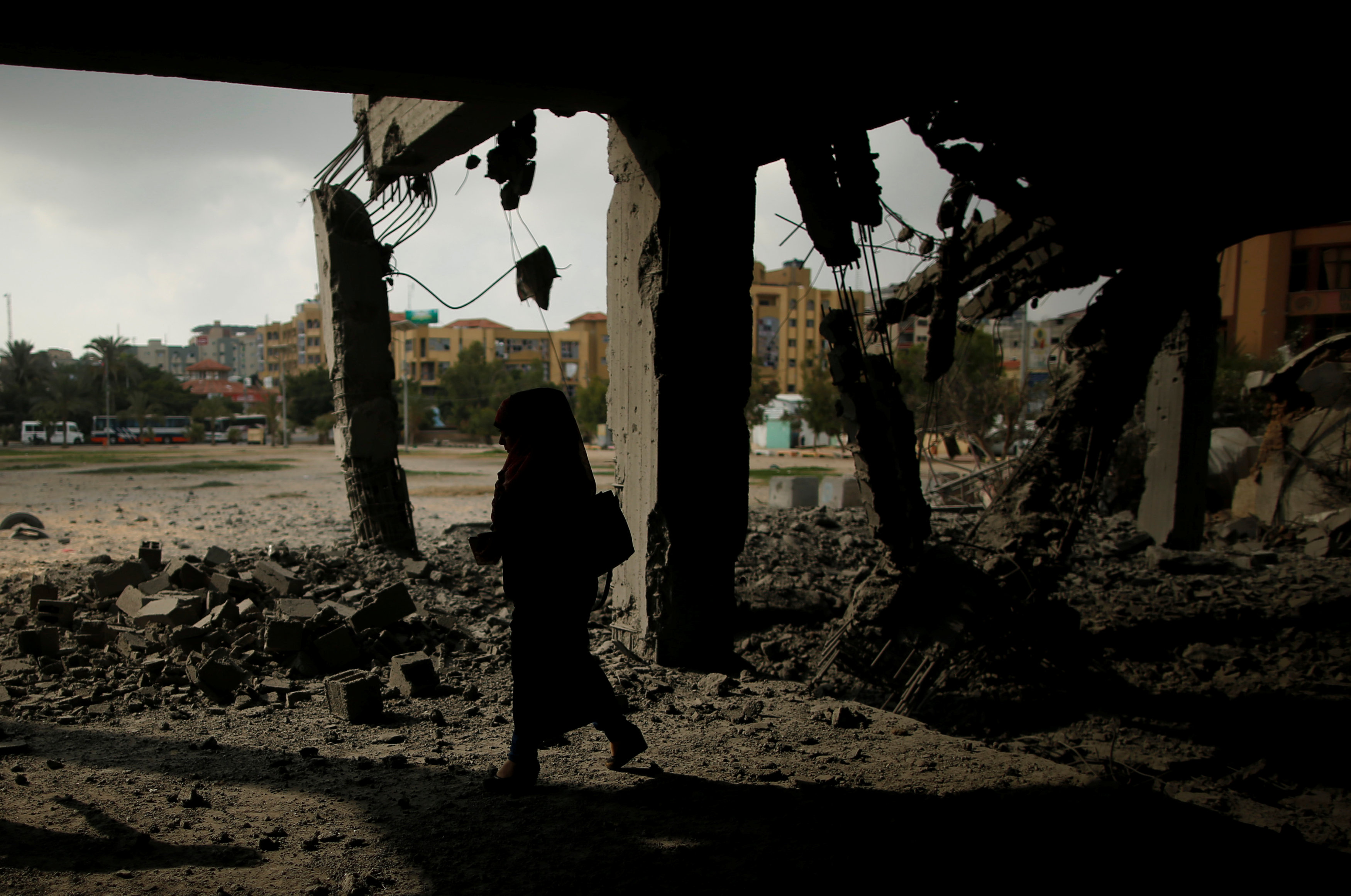 A Palestinian woman passes a building that was destroyed by Israeli air strikes in Gaza City July 15, 2018. REUTERS/Suhaib Salem