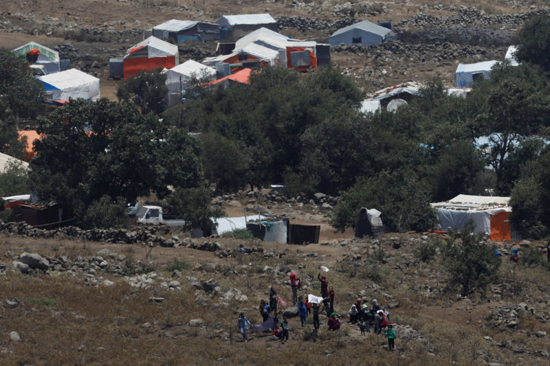 People wave white cloths next to the refugee tents erected near the border fence between Israel and Syria from its Syrian side as it is seen from the Israeli-occupied Golan Heights near the Israeli Syrian border July 17, 2018. REUTERS/Ronen Zvulun