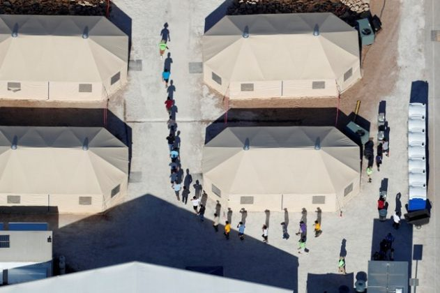 "FILE PHOTO: Immigrant children, many of whom have been separated from their parents under a new ""zero tolerance"" policy by the Trump administration, are shown walking in single file between tents in their compound next to the Mexican border in Tornillo, Texas. REUTERS/Mike Blake"
