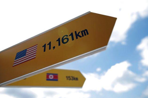 Directional signs bearing North Korean and U.S. flags are seen near the demilitarized zone in Paju, South Korea, June 12, 2018. REUTERS/Kim Hong-Ji
