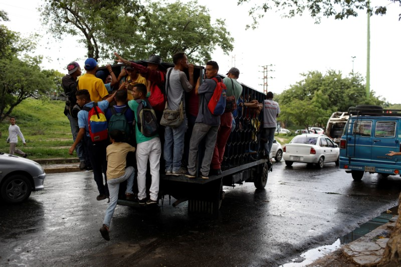 Commuters ride on a cargo truck used as public transportation in Valencia, Venezuela July 11, 2018. Picture taken July 11, 2018. REUTERS/Marco Bello