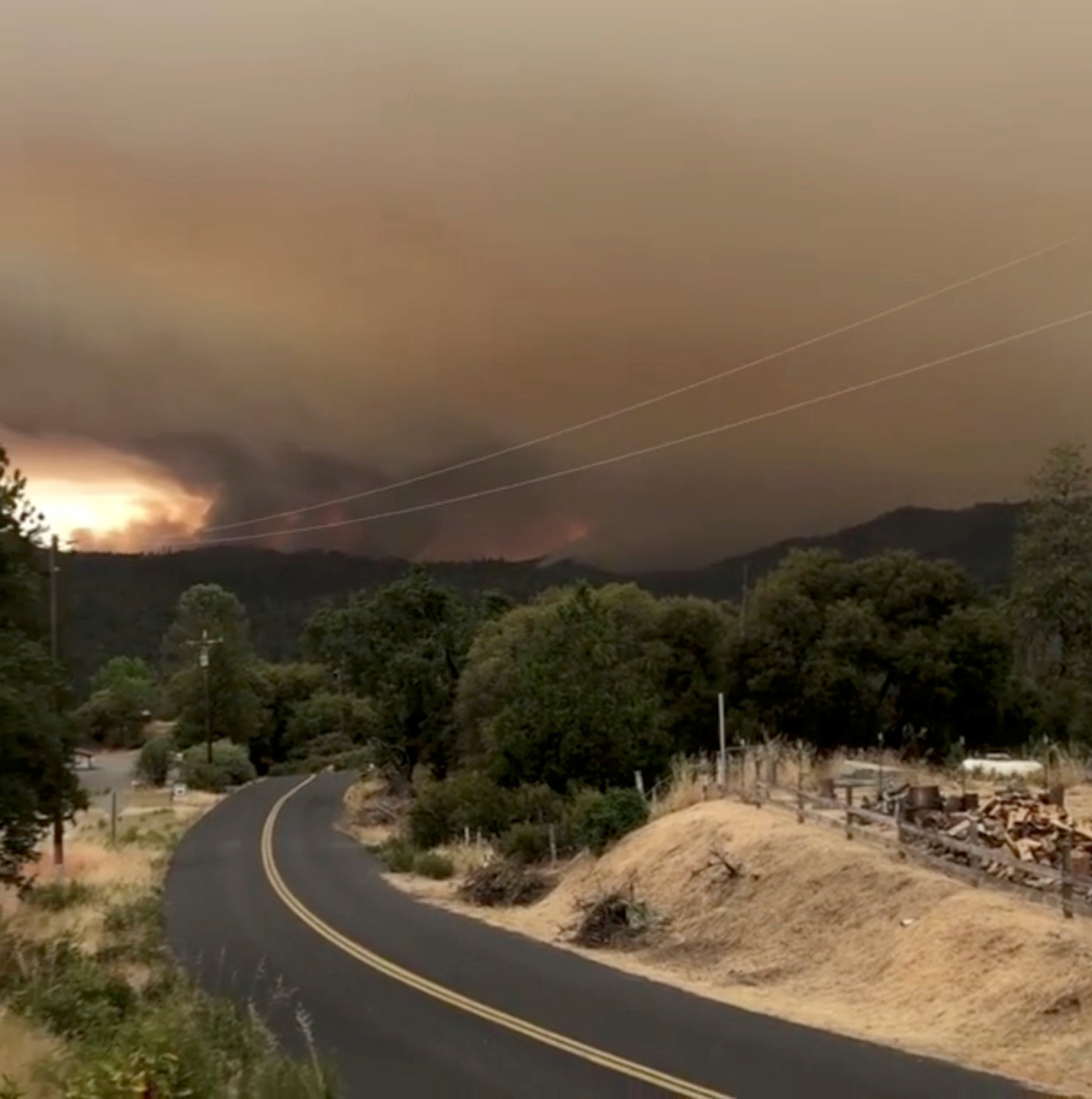 Flames and smoke rise from a treeline in Mariposa County, California, U.S., July 17, 2018 in this still image taken from a social media video obtained July 18, 2018. INSTAGRAM/@JSTETTS/via REUTERS