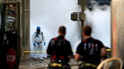 New York Fire Department watch as an emergency responder examines the scene near a steam pipe explosion in Midtown Manhattan, New York City, U.S., July 19, 2018. REUTERS/Brendan McDermid
