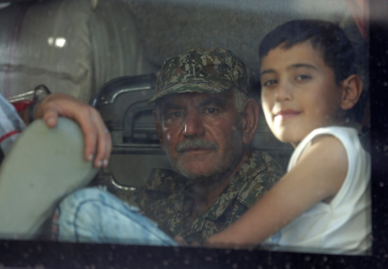 A fighter loyal to President Bashar al Assad and a child are seen in a bus as they are evacuated from the villages of al-Foua and Kefraya, Syria July 19, 2018. REUTERS/Khalil Ashawi