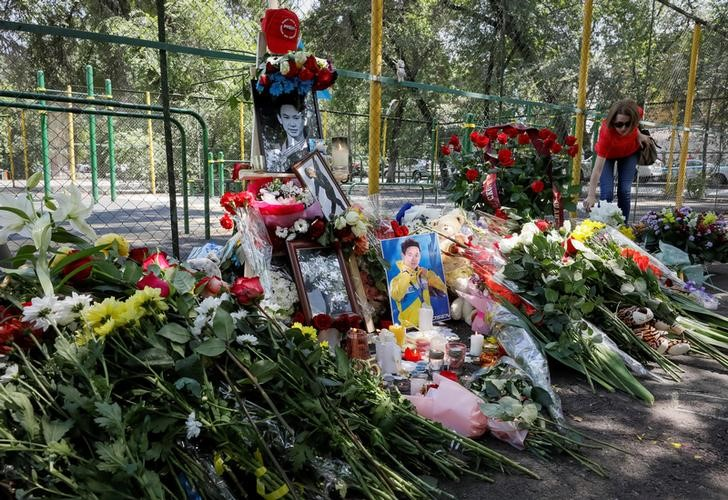 A woman places flowers at the site of the assassination of Kazakhstan's Olympic figure skater Denis Ten in Almaty, Kazakhstan July 20, 2018. REUTERS/Shamil Zhumatov - RC1B8C889C90