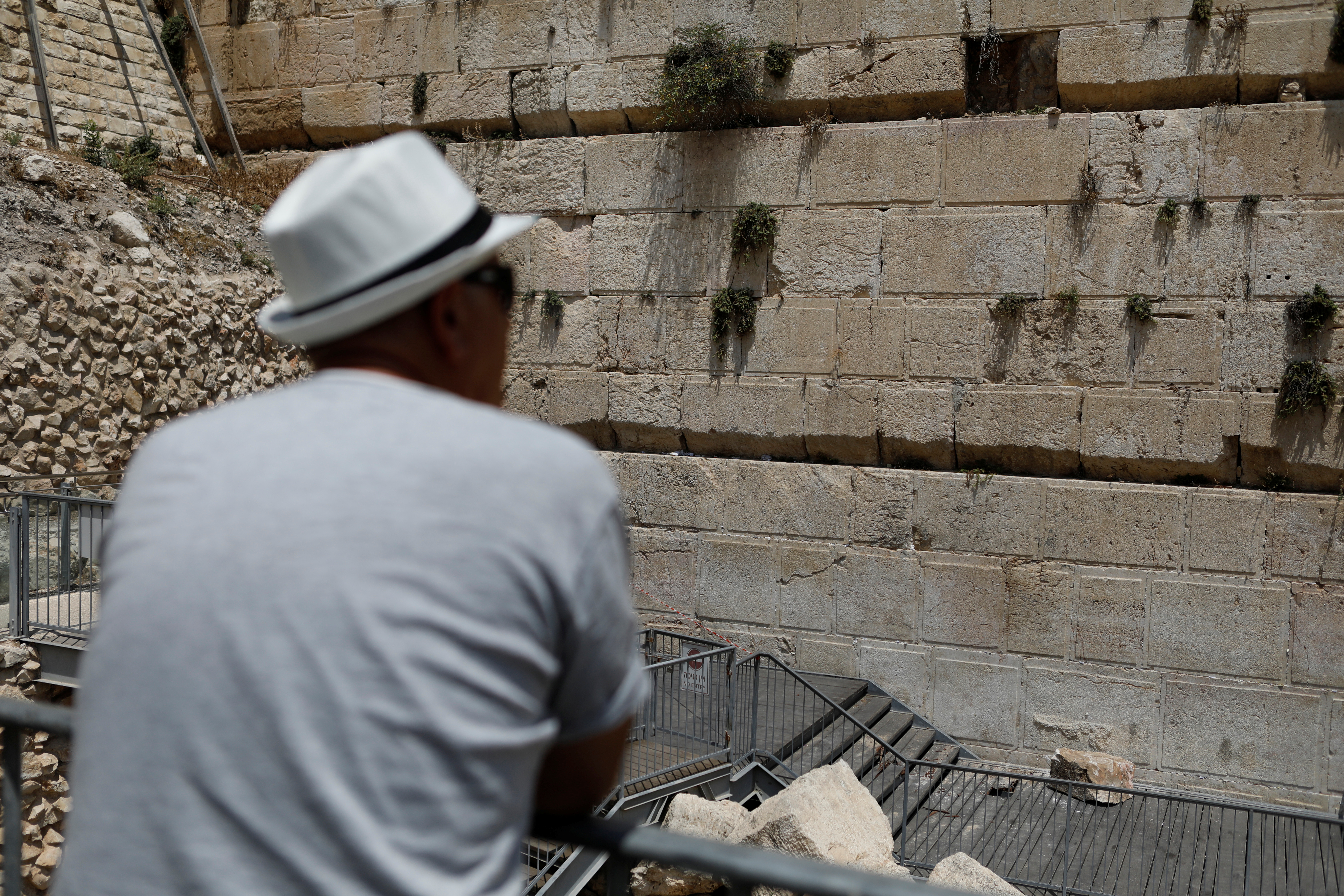 A man looks at a stone that fell off the Western Wall in Jerusalem's Old City, July 23, 2018. REUTERS/ Nir Elias