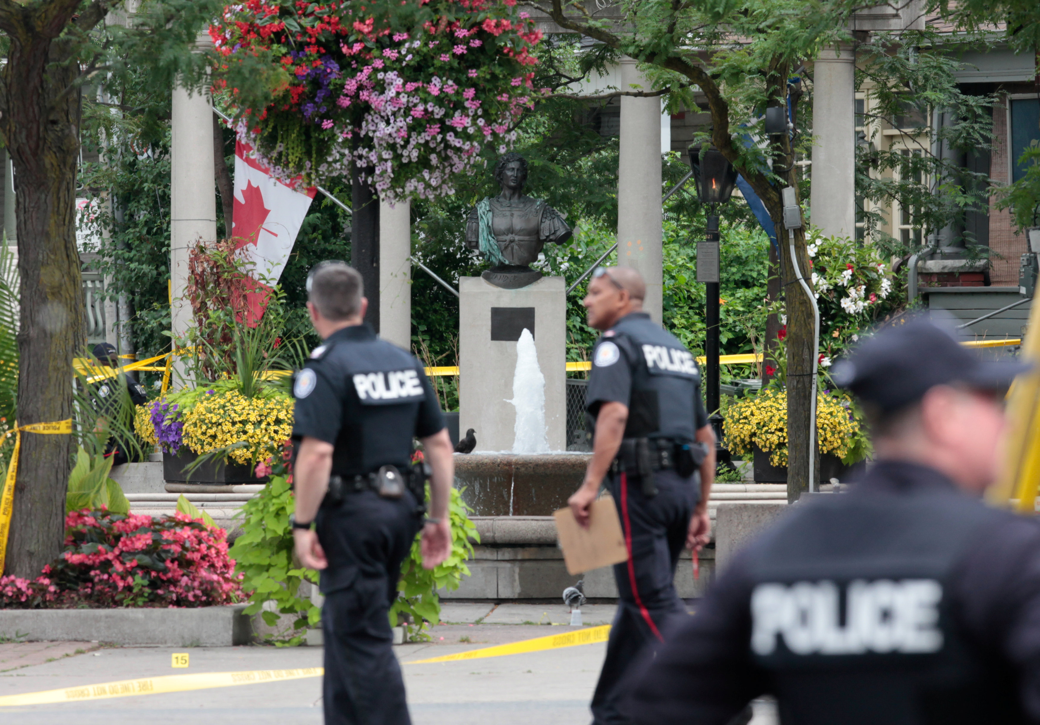 Police officers walk past Alexander the Great Parkette while investigating a mass shooting on Danforth Avenue in Toronto, Canada, July 23, 2018. REUTERS/Chris Helgren