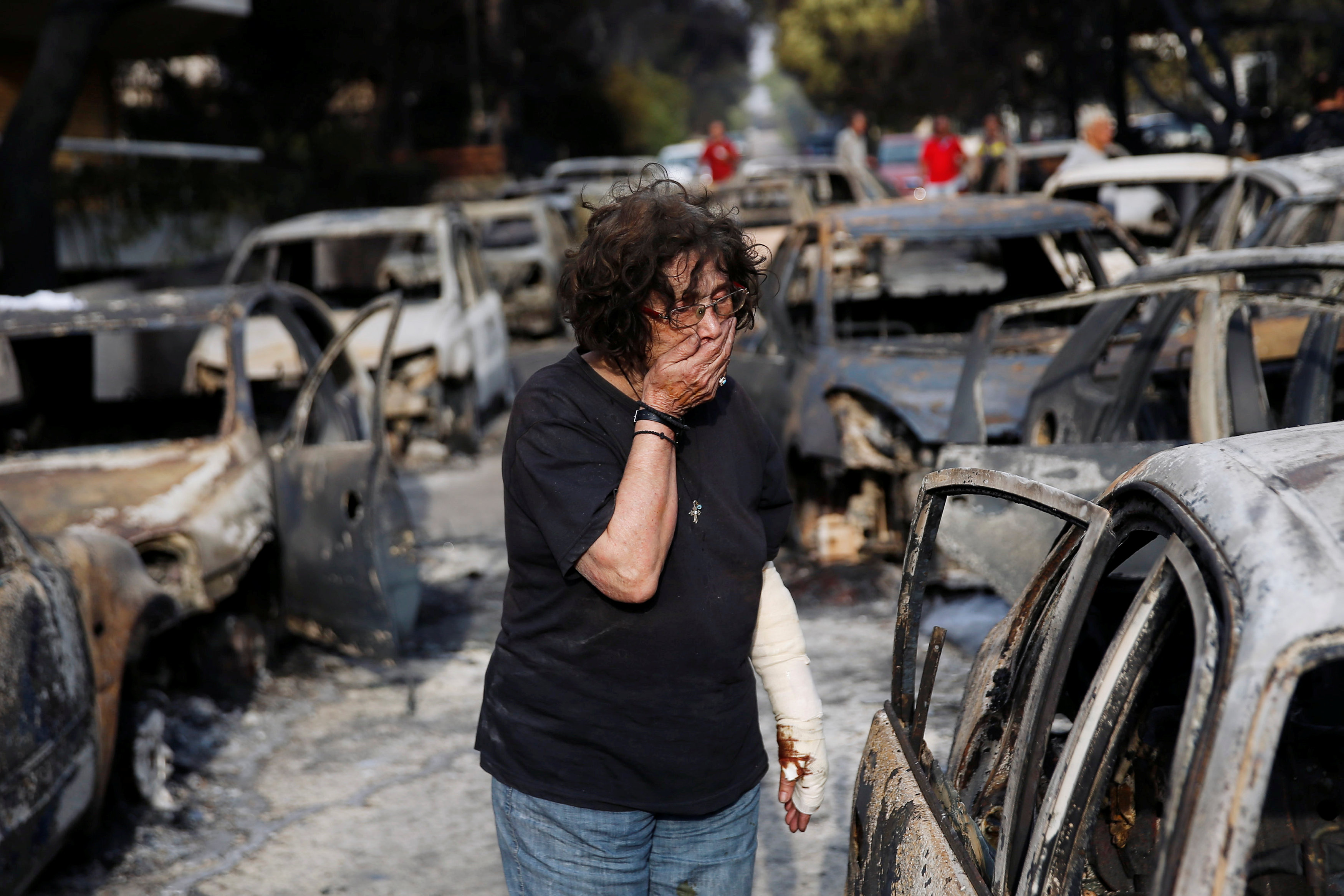 A woman reacts as she tries to find her dog, following a wildfire at the village of Mati, near Athens, Greece July 24, 2018. REUTERS/Costas Baltas