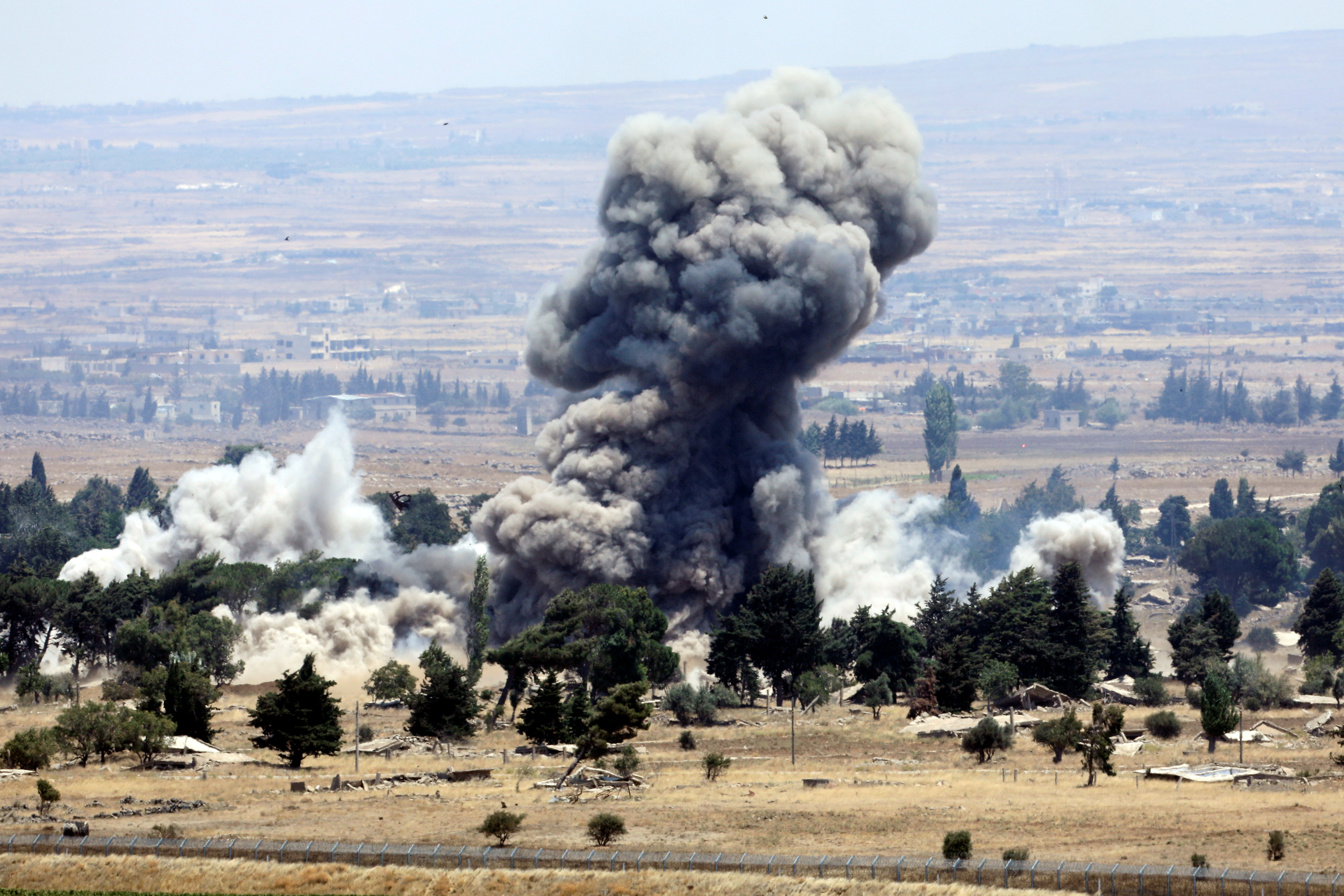 An explosion is pictured at Quneitra at the Syrian side of the Israeli Syrian border, as seen from the Israeli-occupied Golan Heights, July 22. REUTERS/Ronen Zvulun