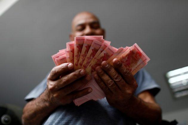 A worker counts Venezuelan bolivar notes at a parking lot in Caracas, Venezuela May 29, 2018. REUTERS/Marco Bell