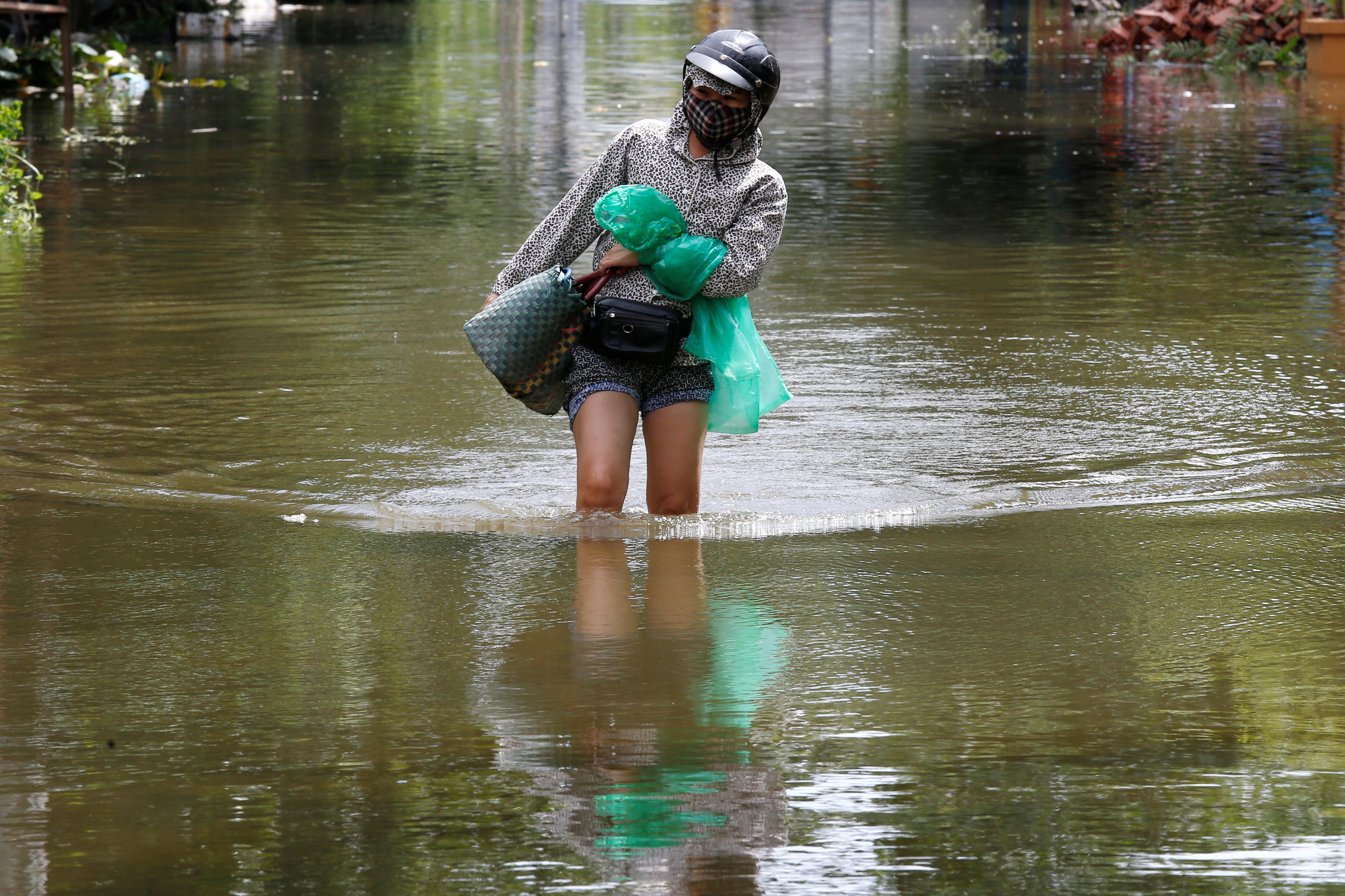 A woman wades through a flooded village after heavy rainfall caused by tropical storm Son Tinh in Ninh Binh province, Vietnam, July 22, 2018. REUTERS/Kham