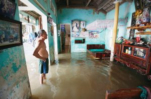 A man stands at his submerged house after heavy rainfall caused by tropical storm Son Tinh at a village outside Hanoi, Vietnam July 24, 2018, REUTERS/Kham