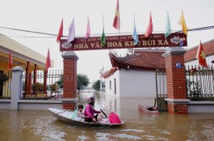 A woman paddles past a submerged temple with her granddaughter after heavy rainfall caused by tropical storm Son Tinh at a village outside Hanoi, Vietnam July 24, 2018, REUTERS/Kham