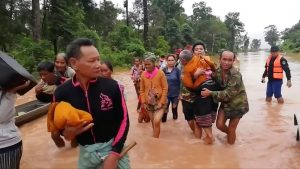 People walk through flooded area after being brought to safety by boat in Sanam Xay district, Attapeu Province, Laos after a hydropower dam under construction in Southern Laos collapsed, in this still picture taken from social media video obtained July 24, 2018. ATTAPEU TODAY/ via REUTERS