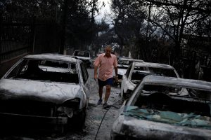 A man walks among burnt cars following a wildfire at the village of Mati, near Athens. REUTERS/Alkis Konstantinidis