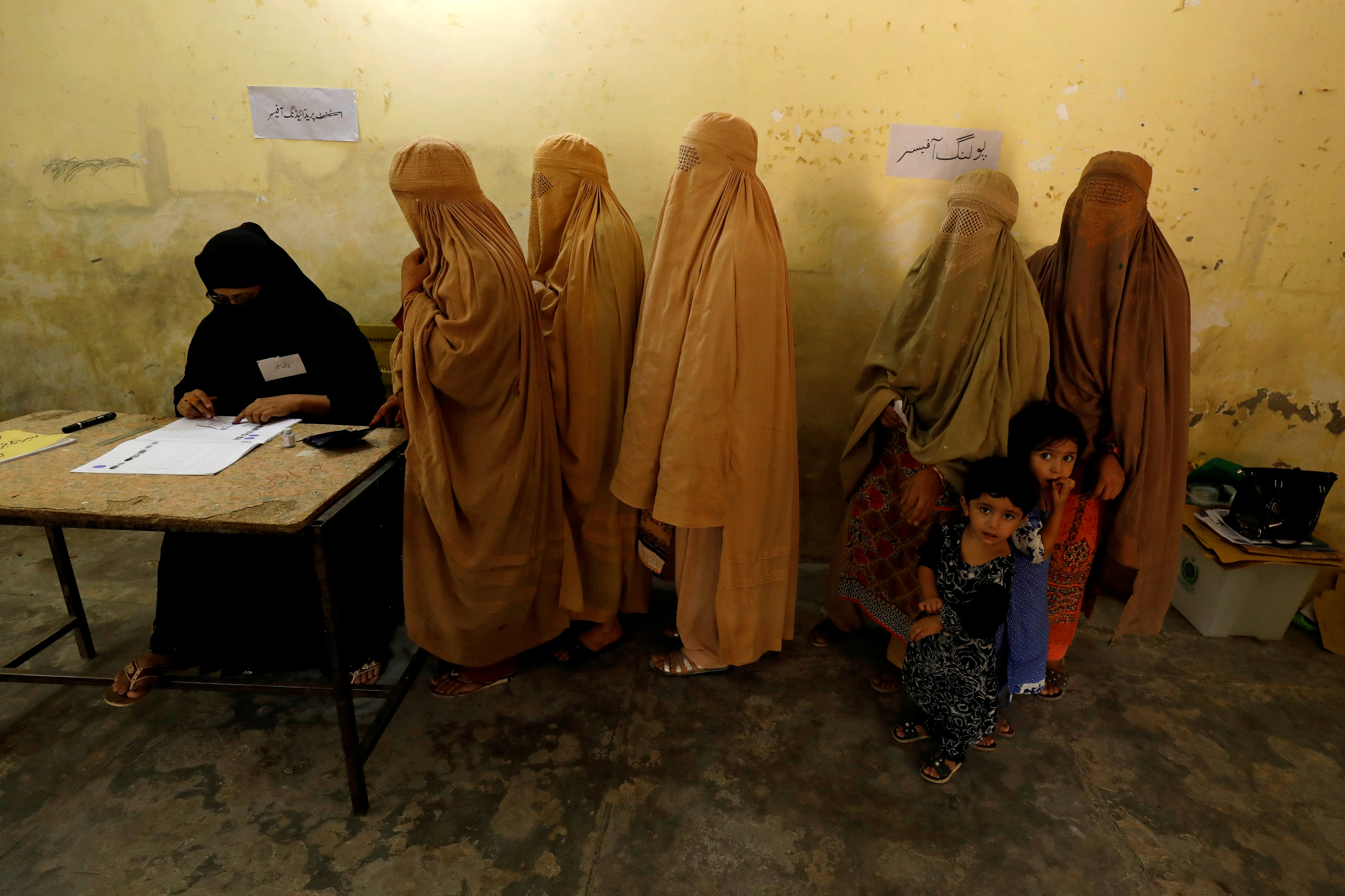 Women, clad in burqas, stand in line to cast their ballot at a polling station during general election in Peshawar, Pakistan July 25, 2018. REUTERS/Fayaz Aziz