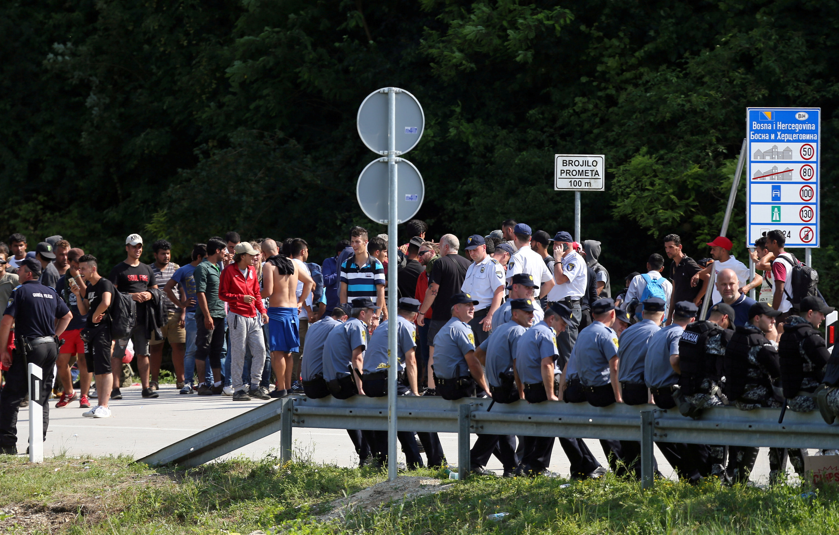FILE PHOTO: Migrants and Bosnian police eye one another in Velika Kladusa, Bosnia, near the border with Croatia, June 18, 2018. REUTERS/Antonio Bronic/File Photo
