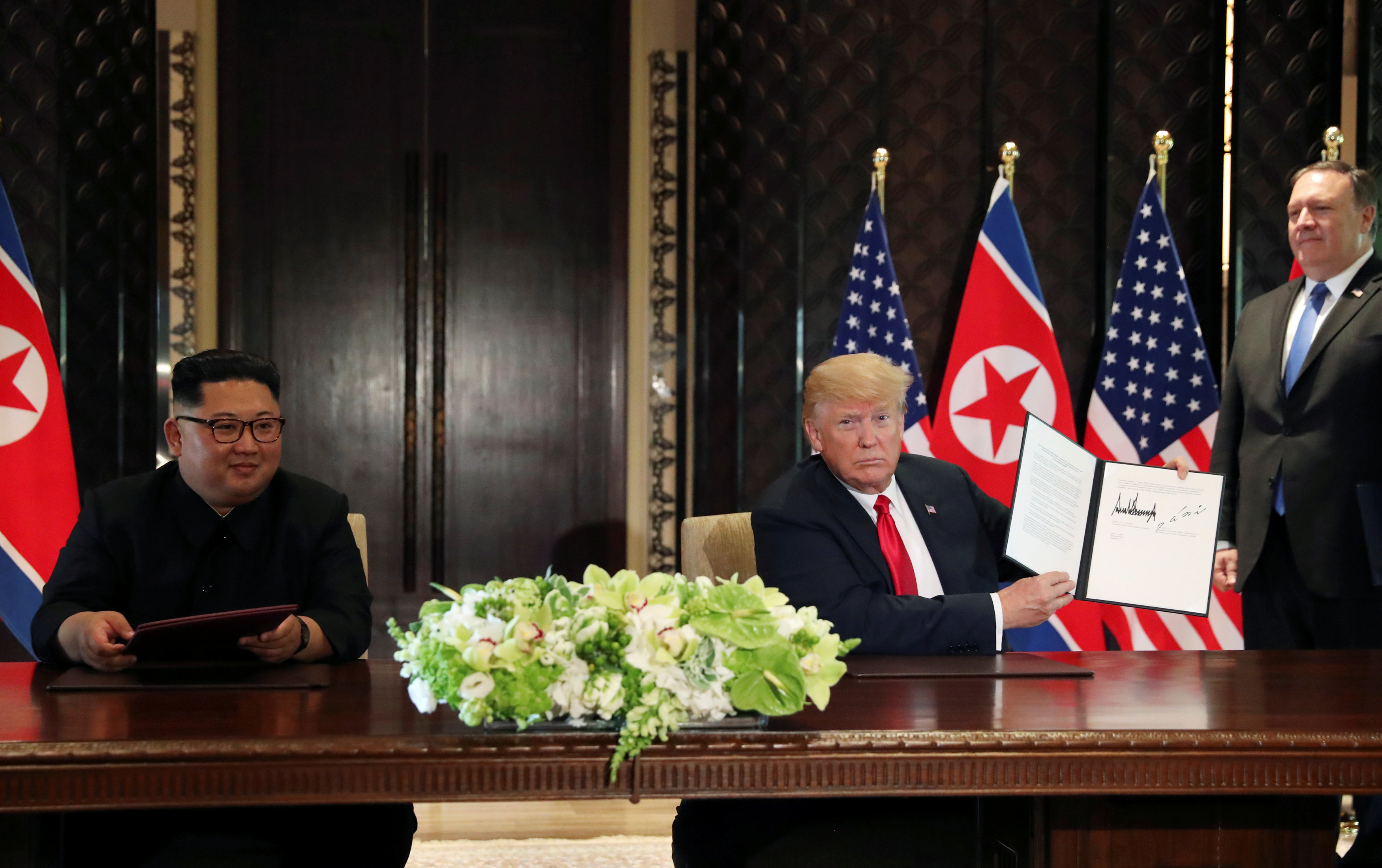 FILE PHOTO: U.S. President Donald Trump shows the document, that he and North Korea's leader Kim Jong Un signed acknowledging the progress of the talks and pledge to keep momentum going, after their summit at the Capella Hotel on Sentosa island in Singapore June 12, 2018. At right is U.S. Secretary of State Mike Pompeo. REUTERS/Jonathan Ernst/File Photo