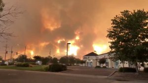 Smoke and flames are seen as a wildfire spreads through Redding, California, the U.S., July 26, 2018, in this still image taken from a video obtained from social media. @pbandjammers/via REUTERS