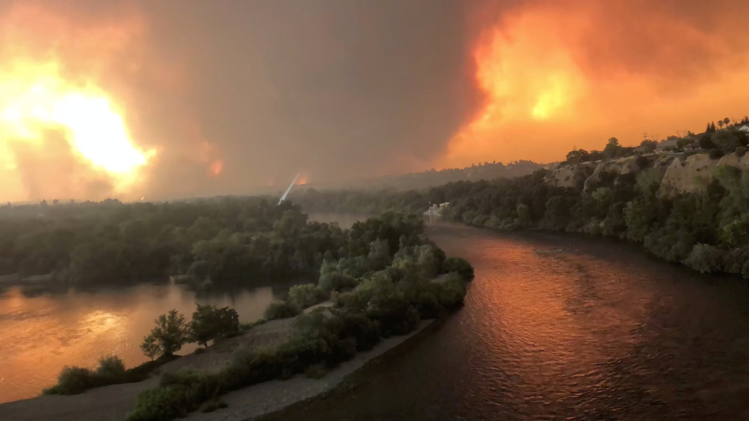 Smoke and flames are seen as a wildfire spreads through Redding, California, the U.S., July 26, 2018, in this still image taken from a video obtained from social media. Cody Markhart/via REUTERS