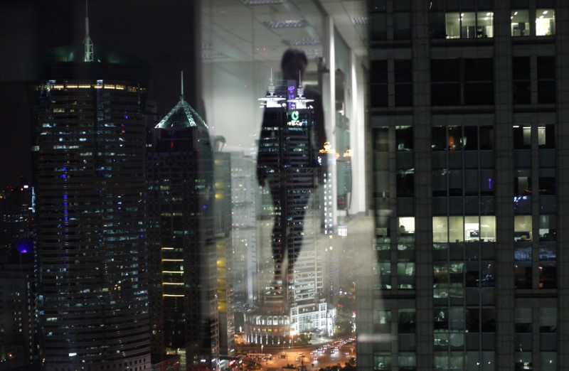 FILE PHOTO: A woman is reflected in a window of an office in Shanghai. REUTERS/Carlos Barria