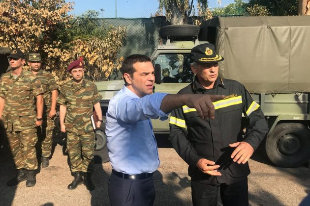 Greek Prime Minister Alexis Tsipras speaks with a firefighter officer as he visits the village of Mati, following a wildfire near Athens, Greece, July 30, 2018. Greek Prime Minister's Press Office/Handout via REUTERS