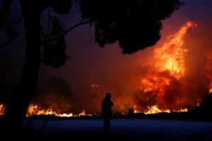 FILE PHOTO: A man looks at the flames as a wildfire burns in the town of Rafina, near Athens. REUTERS/Costas Baltas