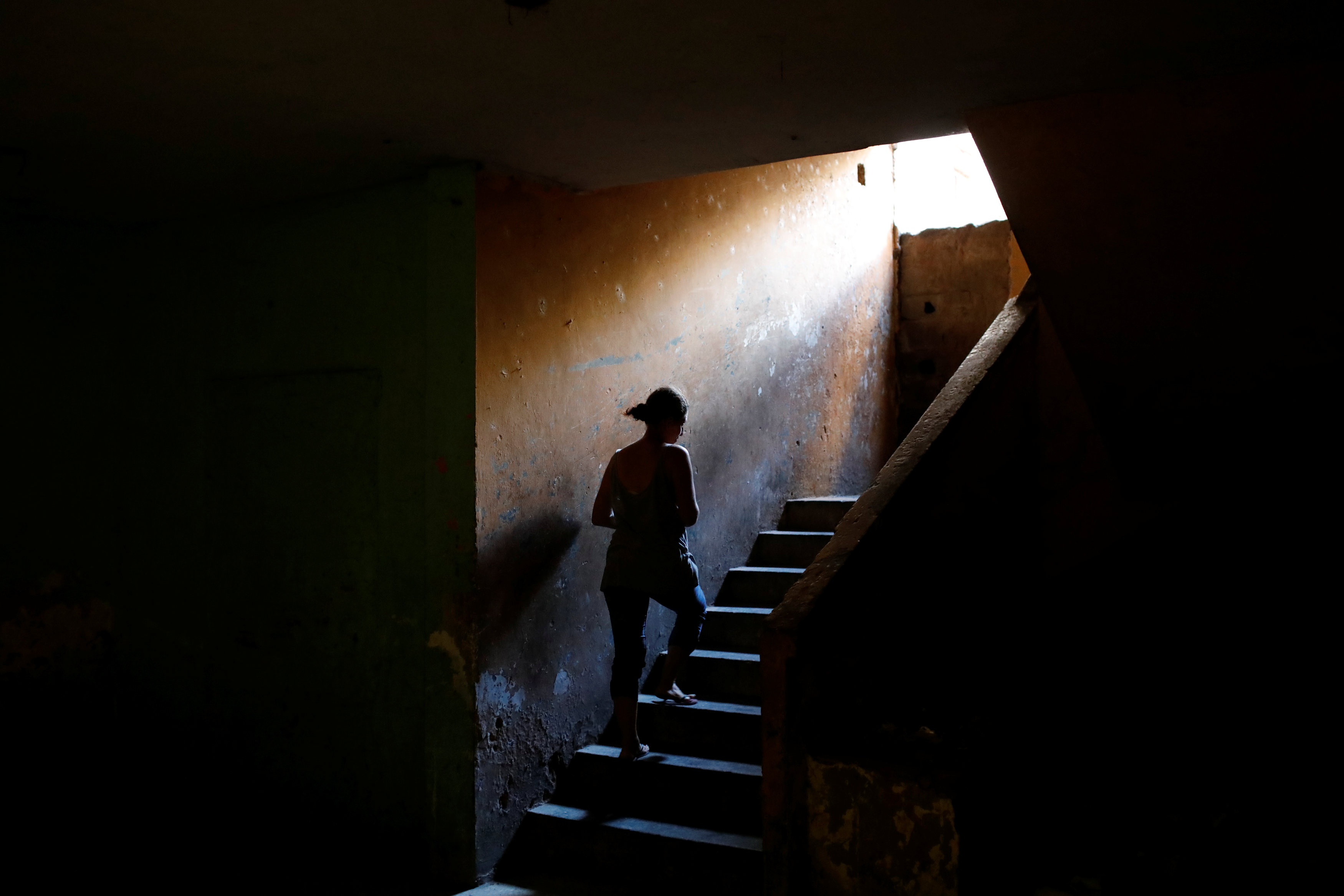 Elizabeth Altuve climbs the stairs at the occupied building where she lives in Maracaibo, Venezuela July 26, 2018. Picture taken July 26, 2018. REUTERS/Marco Bell