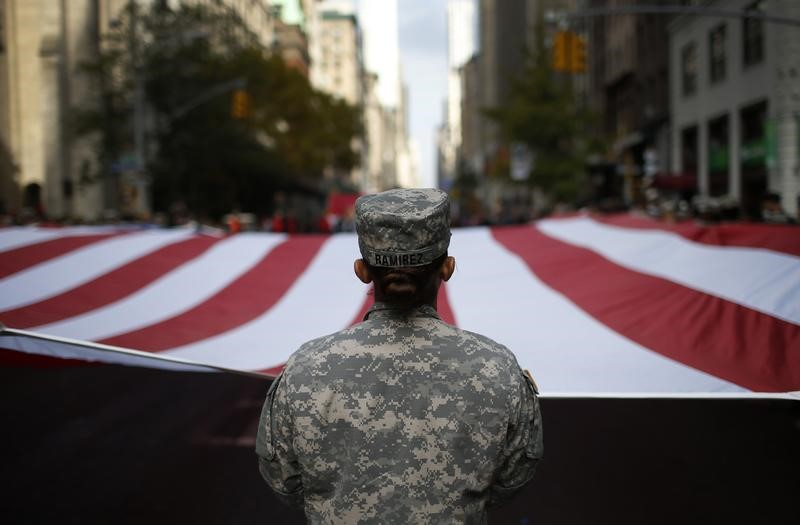 U.S. Army soldiers carry a large U.S. flag as they march in the Veterans Day parade on 5th Avenue in New York November 11, 2014. REUTERS/Mike Segar