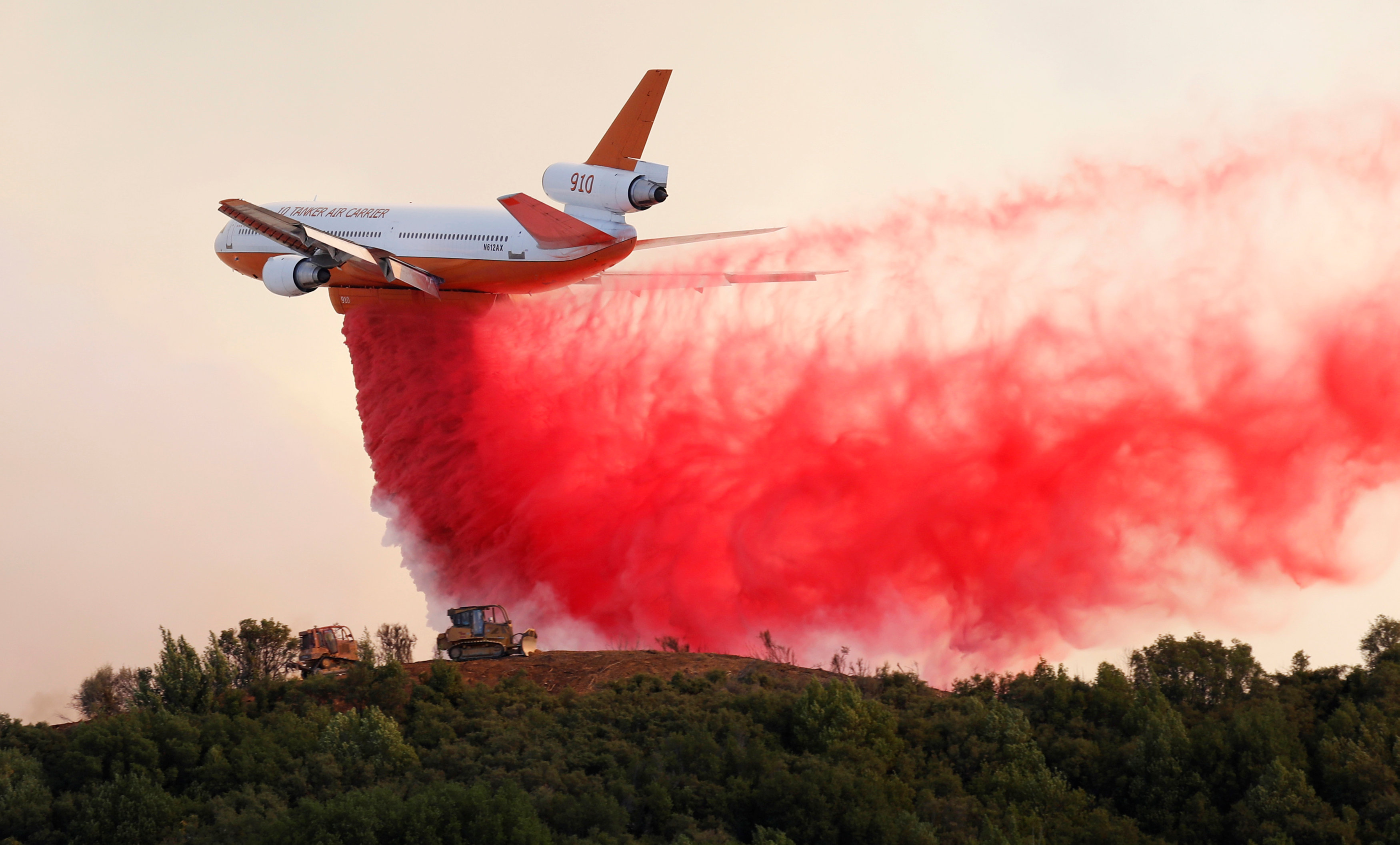 A DC-10 air tanker drops fire retardant along the crest of a hill to protect the two bulldozers below that were cutting fire lines at the River Fire (Mendocino Complex) near Lakeport, California, U.S. August 2, 2018. REUTERS/Fred Greaves