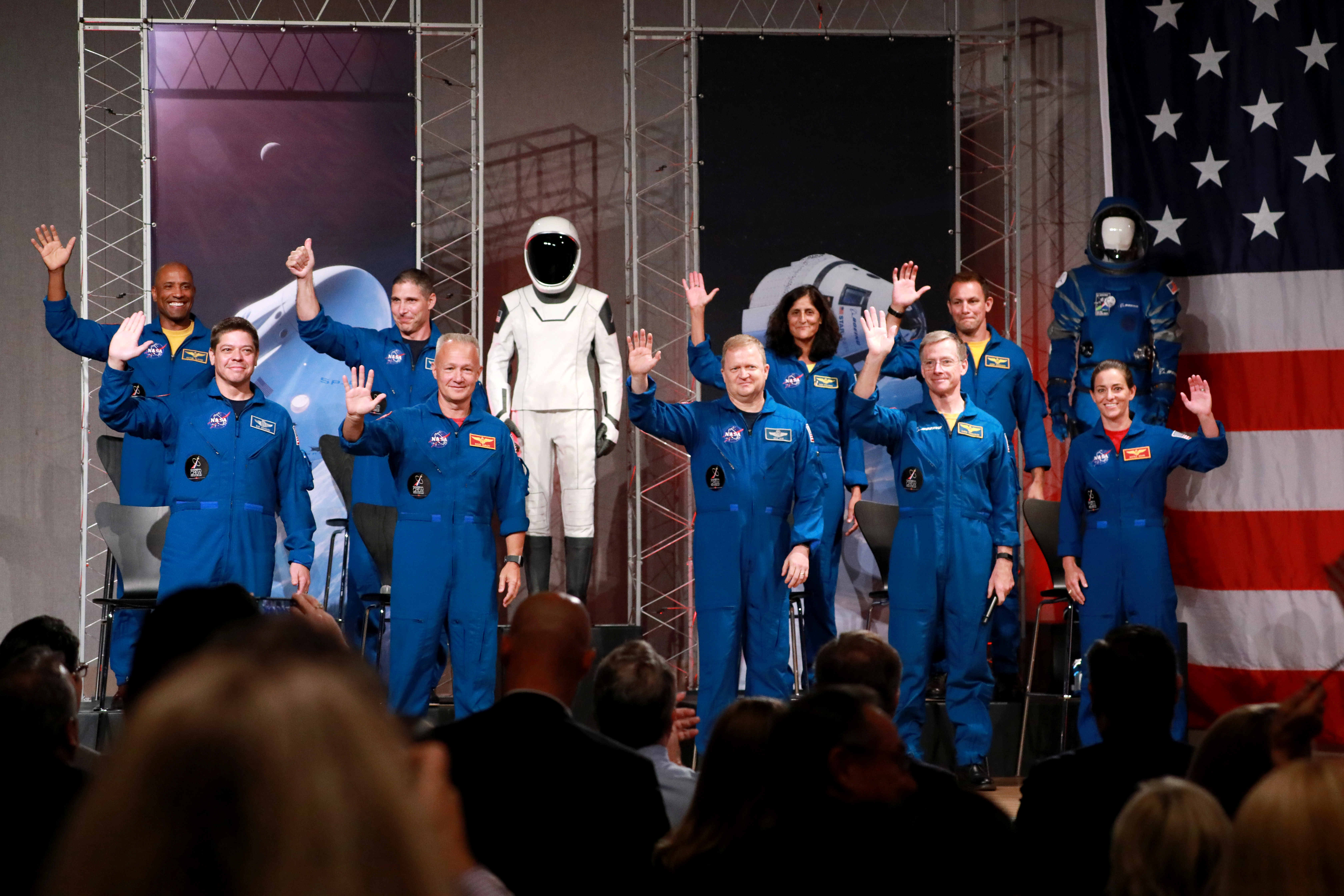 The astronauts assigned to crew the first flight tests and missions of the Boeing CST-100 Starliner and SpaceX Crew Dragon acknowledge the media upon introduction at NASA's Johnson Space Center in Houston, Texas, U.S., August 3, 2018. The astronauts are (L to R): Victor Glover, Robert Behnken, Michael Hopkins, Douglas Hurley, Eric Boe, Sunita Williams, Christopher Ferguson, Josh Cassada, and Nicole Mann. REUTERS/Richard Carson