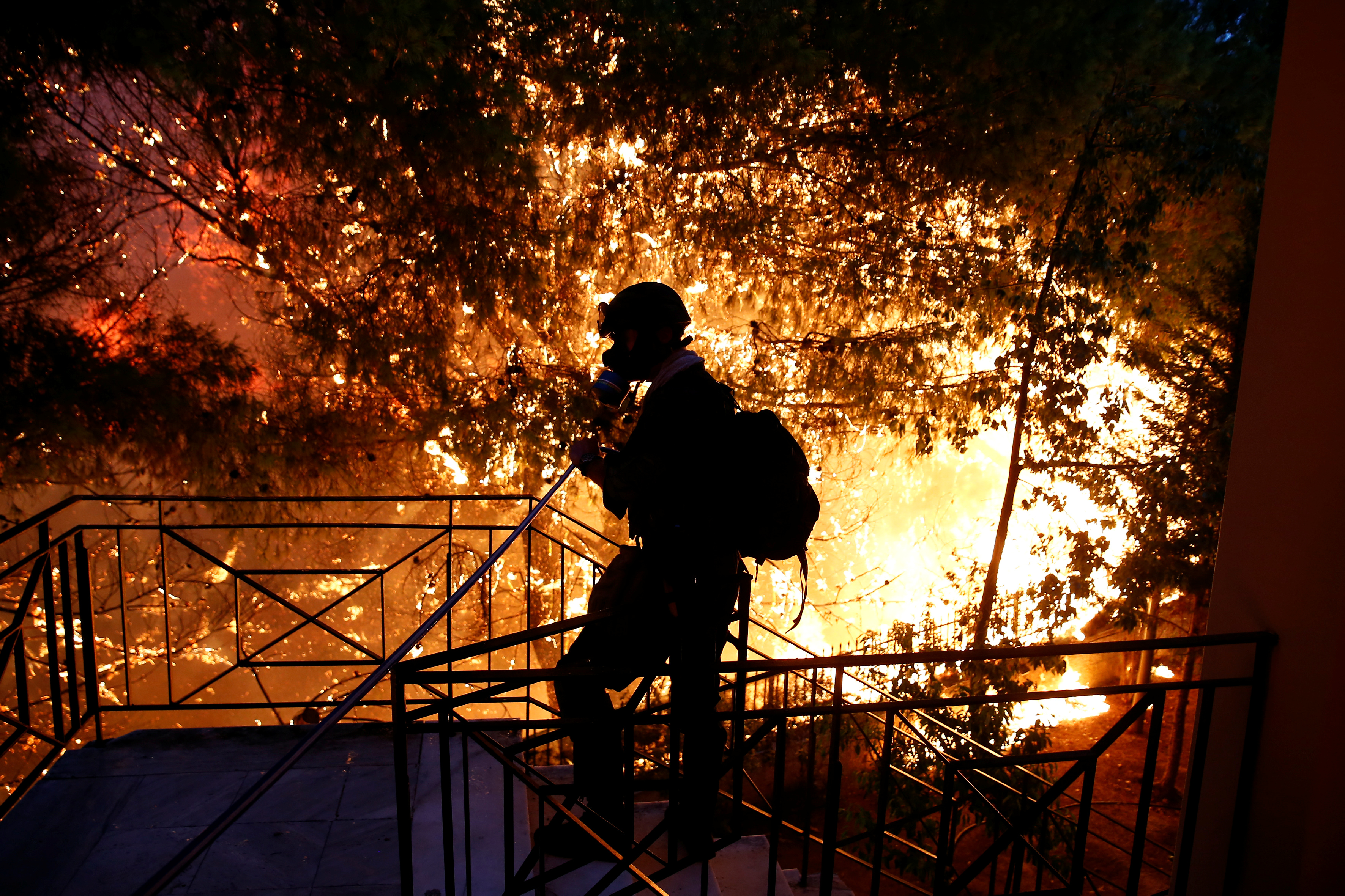 FILE PHOTO: A volunteer throws water through a hose as a wildfire burns in the town of Rafina, near Athens, Greece, July 23, 2018. REUTERS/Costas Baltas